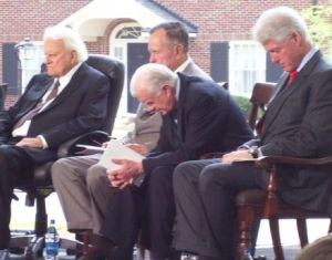 Billy Graham praying with three former presidents